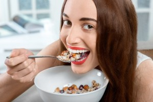 Young positive woman eating granola breakfast on the couch at home. Close-up